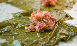 Wrapped pieces of meat in green vine leaves a decorated board Royalty Free Stock Photo