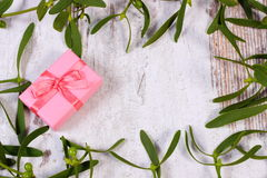 Wrapped pink gift for Christmas and frame of mistletoe on old wooden background Stock Photos