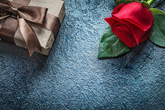 Wrapped present box with brown ribbon red rose on black backgrou Royalty Free Stock Photos