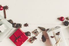 Wrapped present boxes with ornaments with cones anise on white w. Ooden background top view, space for text. christmas flat lay. seasonal greetings card. happy Royalty Free Stock Photo