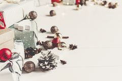 Wrapped present boxes with ornaments pine cones anise and lights. On white wooden background top view, space for text. merry christmas concept. seasonal Stock Photos