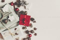 Wrapped present boxes with ornaments pine cones anise on white w. Ooden background top view, space for text. christmas flat lay. seasonal greetings card. happy Stock Photography