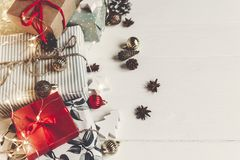 Wrapped present boxes with ornaments pine cones anise on white w. Ooden background with lights top view, space for text. christmas flat lay. seasonal greetings Stock Photo