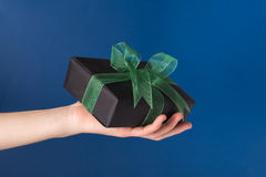 Wrapped present in a hand. Wrapped gift box in a hand over blue background Royalty Free Stock Images