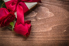Wrapped present with red ribbon natural bloomed roses holiday co Stock Photography