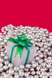 Wrapped present on silver pearls Royalty Free Stock Image