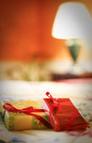 Wrapped presents on a bed. Two small wrapped presents on a bed, with blurred lamp and orange wall in the background Stock Photography