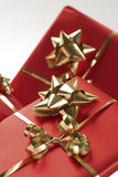 Wrapped presents and bows. A view of presents or gift boxes wrapped in red paper and tied with golden ribbons and bows Royalty Free Stock Photos