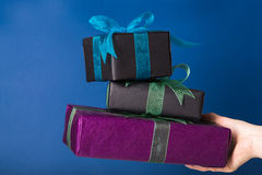 Wrapped presents in a hand. Three wrapped gift boxes in a hand over blue background Stock Images
