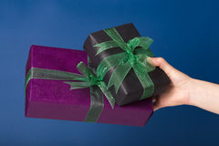 Wrapped presents in a hand. Two wrapped gift boxes in a hand over blue background Royalty Free Stock Photography