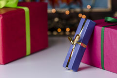 Wrapped presents. Three presents wrapped in blue, red and magenta. Focus is on the golden bowknot, which complements the twinkles in the background Stock Photos