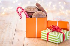 Wrapped presents with Xmas sweets. Ton of colorful gifts, one opened full with gingerbread and Xmas candies, laid on a wooden background, surrounded by blurred Royalty Free Stock Photo