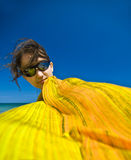 Wrapped in scarf. Pretty young woman with sunglasses on the beach, wrapped in yellow scarf blown by the summer breeze Royalty Free Stock Photography
