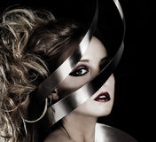 Wrapped in Silver. Beautiful model looking through a silver sculpture on a black background Stock Image