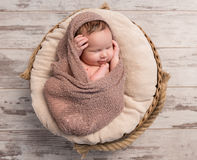 Wrapped sleepy baby with folded legs and hands on head. Top view Stock Photo