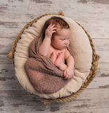 Wrapped sleepy baby with folded legs and hands on head. Top view Royalty Free Stock Images