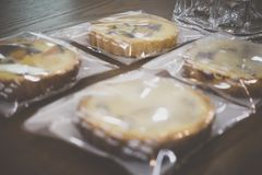 Wrapped sweet pumpkin and sweet potato pies on wooden table stock photography