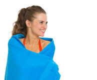 Wrapped in towel smiling young woman in swimsuit Stock Photo