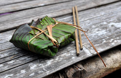 Wrapped traditional food. Banana leaf wrapped traditional food on wooden table stock photos