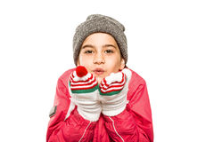 Wrapped up little girl blowing over hands Royalty Free Stock Photo