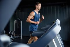 Wrapped up in Training. Full length portrait of muscular sportsman listening to music in headphones and using treadmill while wrapped up in training at modern Stock Image