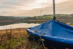 A wrapped up Yacht waits to be taken out on the reservoir in the Peak District during a relaxing sunset stock images