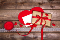 Wrapped vintage gift box with red ribbon bow and gift card on the wooden table Stock Image