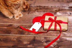 Wrapped vintage gift box with red ribbon bow and gift card on the wooden table Stock Photo