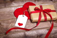 Wrapped vintage gift box with red ribbon bow and gift card on the wooden table Royalty Free Stock Images