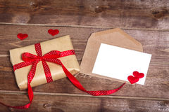 Wrapped vintage gift box with red ribbon bow and gift card on the wooden table Stock Photos