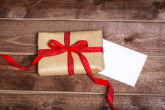 Wrapped vintage gift box with red ribbon bow and gift card on the wooden table Stock Photography