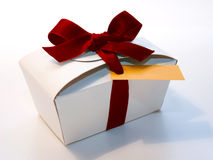Wrapped vintage gift box with red ribbon bow on light background Royalty Free Stock Images