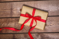 Wrapped vintage gift box with red ribbon bow on wooden background can use on valentine day Royalty Free Stock Images