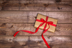 Wrapped vintage gift box with red ribbon bow on wooden background can use on valentine day Stock Images
