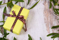 Wrapped yellow gift for Christmas and frame of mistletoe on old wooden background Royalty Free Stock Image