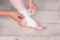 Wrapping an ankle in a bandage Royalty Free Stock Photo