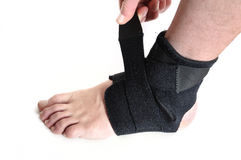 Wrapping a Black Ankle Brace. Isolated on White Royalty Free Stock Photos