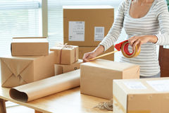 Wrapping boxes. Cropped image of woman wrapping boxes to send via mail royalty free stock photo