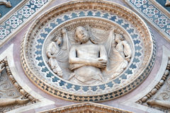 Wrapping Christ in his shroud, Portal on the side-wall of Florence Cathedral Stock Photos