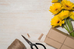 Wrapping flowers gift over wooden background. Top view with copy Stock Photography