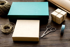 Wrapping gifts in box for holiday on wooden background Stock Photography