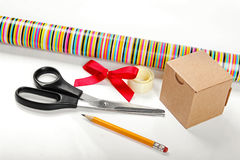 Wrapping paper with scissors and gift on the table Royalty Free Stock Images