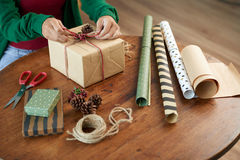 Wrapping present. Creative woman using craft paper, berries and cones when wrapping present stock images