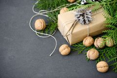 Wrapping rustic eco Christmas packages with brown paper, string and natural fir branches on dark background. Flat lay, free space Stock Image