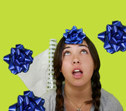 Wrapping time. Teenage girl looking up with bows falling around her Royalty Free Stock Photo
