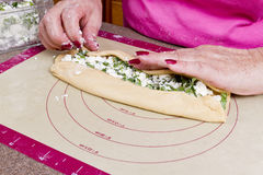 Wrapping the Turkish Pide. Older lady hands are wrapping Turkish feta cheese Pide pockets Stock Photo