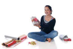 Wrapping Up Christmas. Preteen girl surrounded by simple wrapping supplies, showing off the gift she's just wrapped.  Isolated on white Royalty Free Stock Images