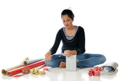 Wrapping Up Christmas. A preteen girl wrapping a gift to give at Christmas Royalty Free Stock Photo
