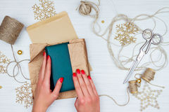 Wrapping up christmas gift. Royalty Free Stock Images