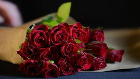 Wrapping Valentine Red Roses. In natural brown paper, closeup stock video